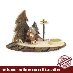 Auf seinem Schlitten, fährt der gedrechselte Elch, der Firma Hennig, zwischen Rindenbäumen hindurch. Der Kerzenleuchter als Baumscheibe, unbehandelt, das Holz in seiner natürlichen Form.