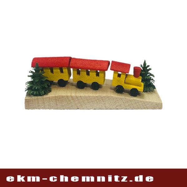 Eine kleine Eisenbahn in gelb auf einem Miniatur Brettchen.