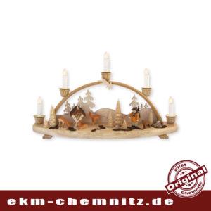 Der traditionelle Schwibbogen mit 5 Kerzen. Der Waldarbeiter genießt die Ruhe des Waldes und beobachtet mit seinem Hund die äsenden Rehe.