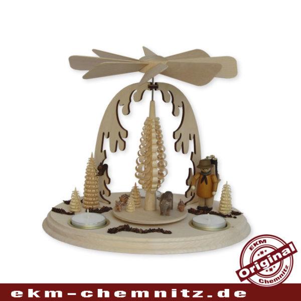 Im Wald tümmeln sich Wildschweine, als eine Waldarbeiter auf sie trifft. Ein klassisches Motiv auf einer Weihnachtspyramide.